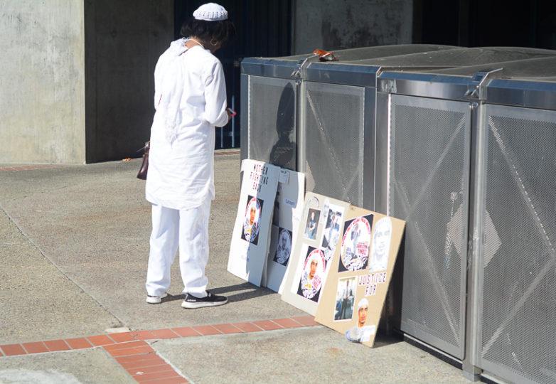 Kanikah LeMon-Jones, antigua profesora de Sahleem Tindle, mira sus fotos durante la protesta en se organizó en su honor tras haber sido asesinado por un policía del BART el 3 de enero. Foto Aaron Levy-Wolins