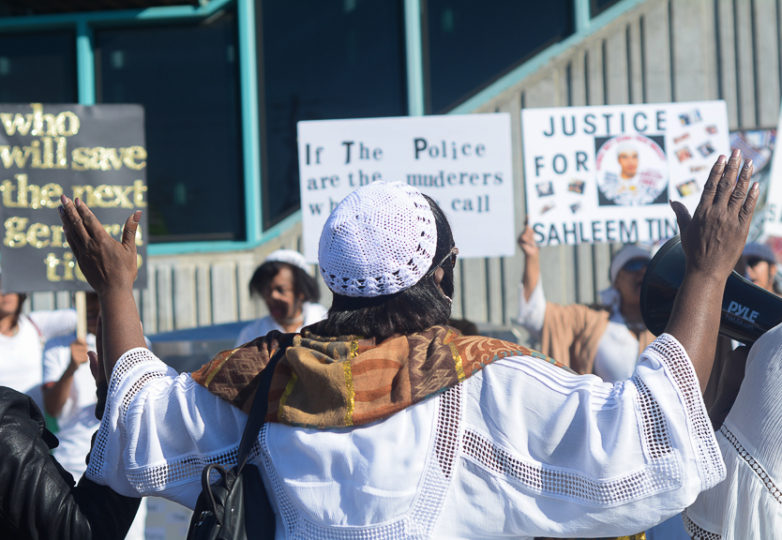 A family member of slain Oakland man Sahleem Tindle holds her hands up in prayer during a vigil-protest  in front of the West Oakland BART Station on Feb. 13, 2018. Photo Aaron Levy-Wolins