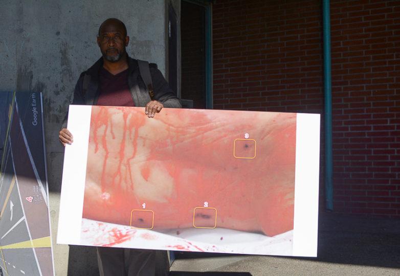 Juan Sigler, un investigador privado que representa a la familia de Sahleem Tindle, sostiene una fotografía en la que se ve la espalda de Tindle y los tres disparos que acabaron con su vida. Foto Aaron Levy-Wolins
