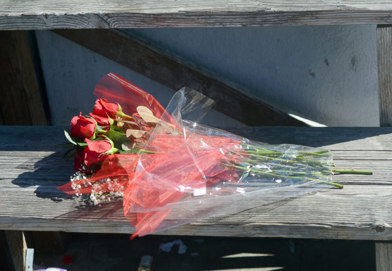 A bouquet of flowers rests on a wooden fixture honoring Sahleem Tindle, during a vigil-protest in front of the West Oakland BART Station on 13, 2018. Photo Aaron Levy-Wolins