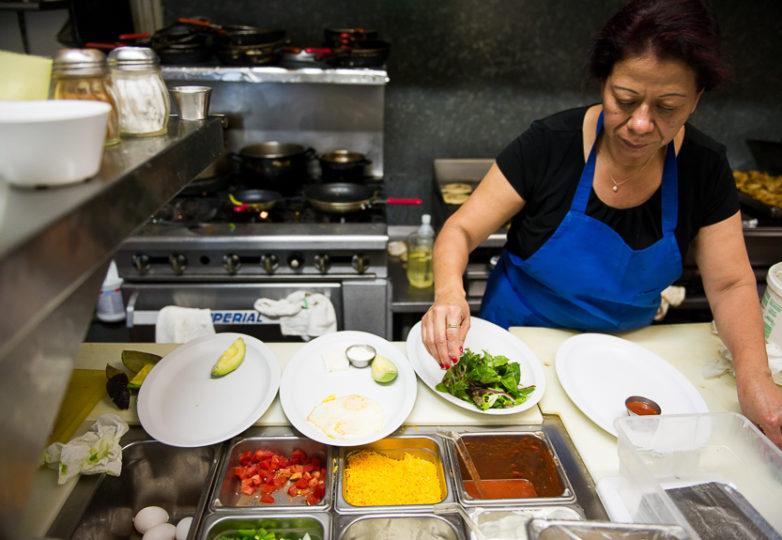 Alba Guerra, propietaria del Restaurante Sunrise, prepara platillos en su negocio. Foto: Beth LaBerge