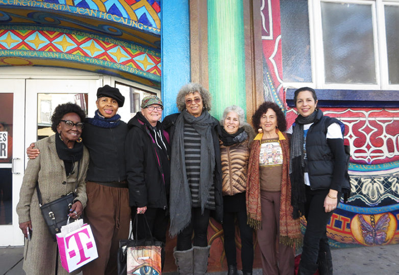Angela Davis (center), who has written the opening essay for the upcoming book on the Women's Building Mural, poses with six of the seven original Mujeres Muralistas: (from left) Edythe Boone, Yvonne Littleton, Susan Cervantes, Juana Alicia, Miranda Bergman and Meera Desai,  in January. Photo: Tatjana Loh