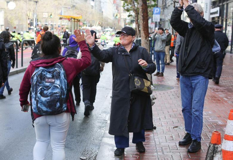 Un simpatizante choca manos con alumnos que marchan en su trayecto hacia el Ghirardelli Square, protestando por la falta de mayor regulación de armas. Foto: Gino Abrajano