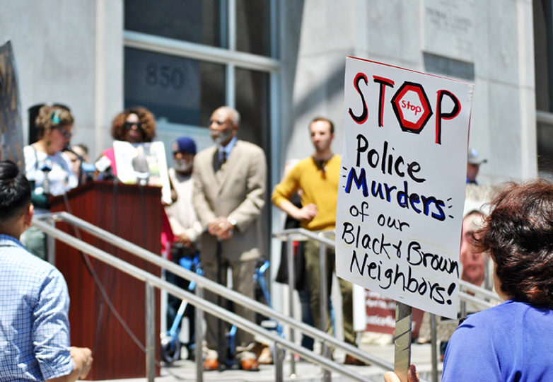 Un manifestante sostiene una pancarta condenando la brutalidad policíaca durante una conferencia de prensa el 29 de mayo en la Sala de Justicia de San Francisco. Foto: Alejandro Galicia Diaz