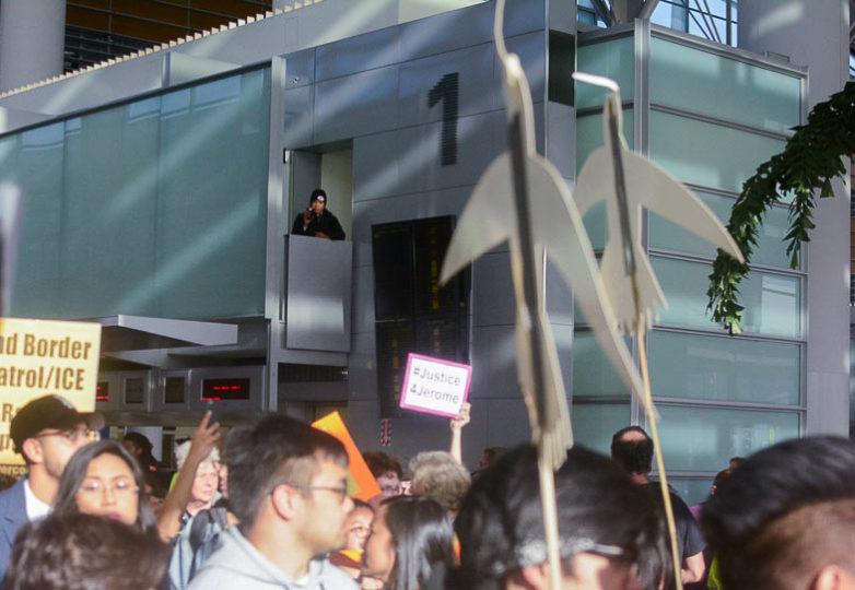 Un miembro de la seguridad graba a los manifestantes durante la protesta por la supuesta tortura y deportación de Jerome Aba. Foto: Aaron Levy-Wolins