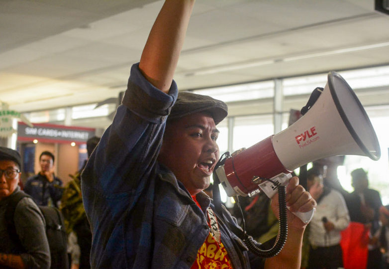 """PJ,"" from the Kabataan Alliance, leads a chant at a protest at SFO on April 23 against the deportation and alleged torture of Jerome Aba. Photo: Aaron Levy-Wolins"