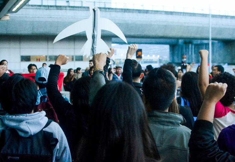 Manifestantes levantan sus puños en solidaridad durante la protesta por la deportación y tortura de Jerome Aba. Foto: Aaron Levy-Wolins