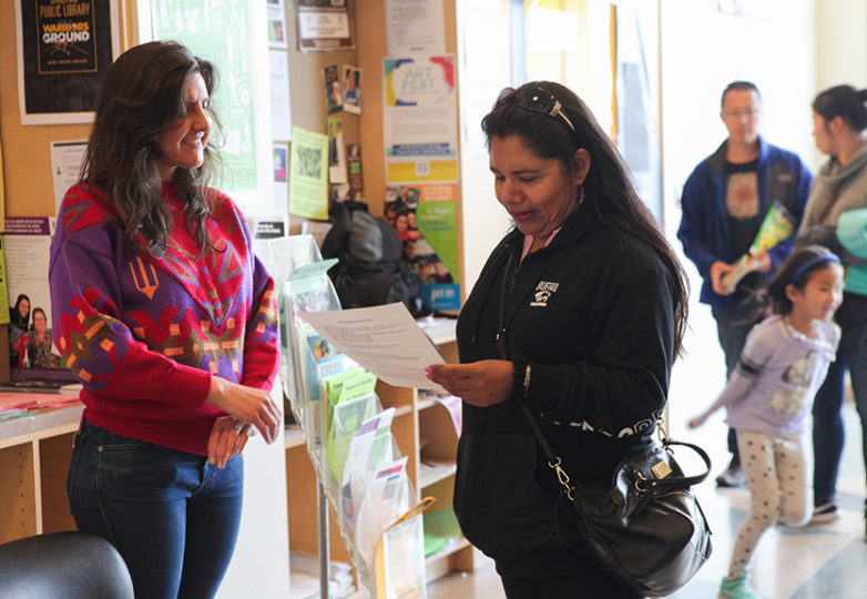 """A journalist and human rights documentarian Madeleine Bair (right) speaks with people during her """"participatory reporting"""" project called El Tímpano, at the Oakland Public Library near Fruitvale BART Station on April 7. Photo: Ekevara Kitpowsong"""