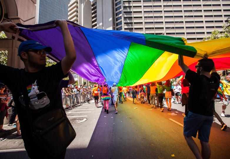 Participantes del Desfile cargan una enorme bandera arcoiris. Foto: Ekevara Kitpowsong