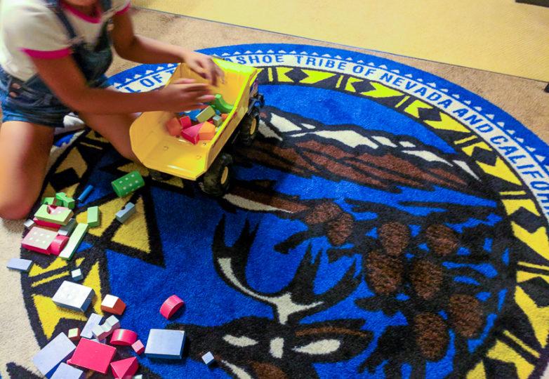 La hija de Gaby juega en un tapete de bienvenida con el sello de la tribu Washoe de Nevada y California, en las Oficinas de San Francisco, el 2 de julio de 2018. Foto: Adriana Camarena