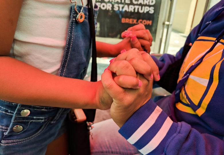 Gaby y su hija tomadas de la mano en una estación del autobús en el Distrito de la Misión. Foto: Adriana Camarena