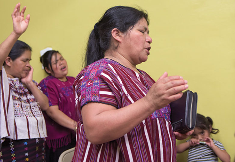 Guadalupe Hernandez stands before women in the Mam community while singing along with the pastor. Photo: Mark Jason Quines