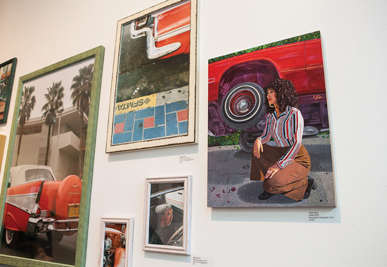 "Artwork and photographs are displayed on the wall during the opening reception of ""Ode to Our Barrio: A Tribute to the Mission District in Painting & Photography."" Photo: Ekevara Kitpowsong"