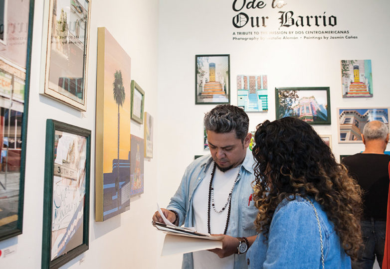 "Executive Director of Acción Latina Josué Rojas chats with an attendee during the opening reception of ""Ode to Our Barrio: A Tribute to the Mission District in Painting & Photography,"" an exhibition showcasing work by two Latina artists; Natalie Alemán and Jasmin Cañas on Saturday, Sept. 1, 2018 at Juan R. Fuentes Gallery in San Francisco's Mission District. Photo: Ekevara Kitpowsong"