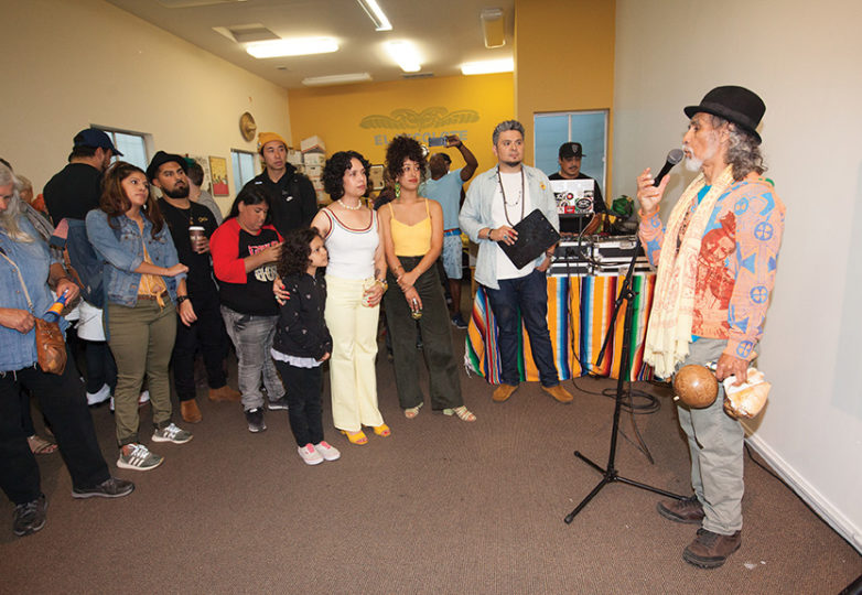 "(Right) Jorge Molina speaks to the audience and gives a blessing during the opening reception of ""Ode to Our Barrio: A Tribute to the Mission District in Painting & Photography."" Photo: Ekevara Kitpowsong"