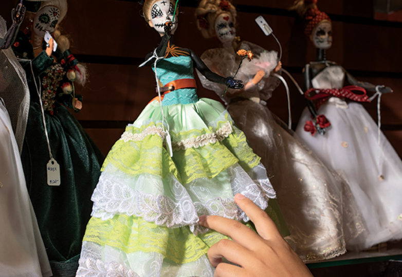 A customer reaches for a doll made by local artist Ana Rivero Rossi, inside Casa Bonampak on Oct. 12, 2018. Photo: Dane Pollok