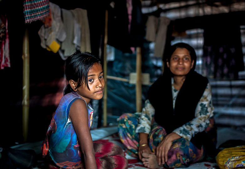 A young Rohingya girl sits inside a shelter with her mother in the Kutupalong refugee camp in Bangladesh on Dec. 18, 2017. Photo: Mike Chen