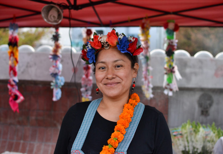A vendor at 24th Street BART Plaza poses for a portrait during Día de Muertos in San Francisco's Mission district, Friday November 2, 2018. Photo: Mabel Jimenez/Calle 24