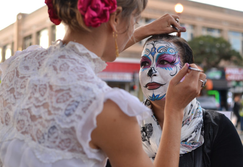A face painting artist works on a sugar skull pattern on 24th Street during Día de Muertos in San Francisco's Mission district, Friday November 2, 2018. Photo: Mabel Jiménez/Calle 24