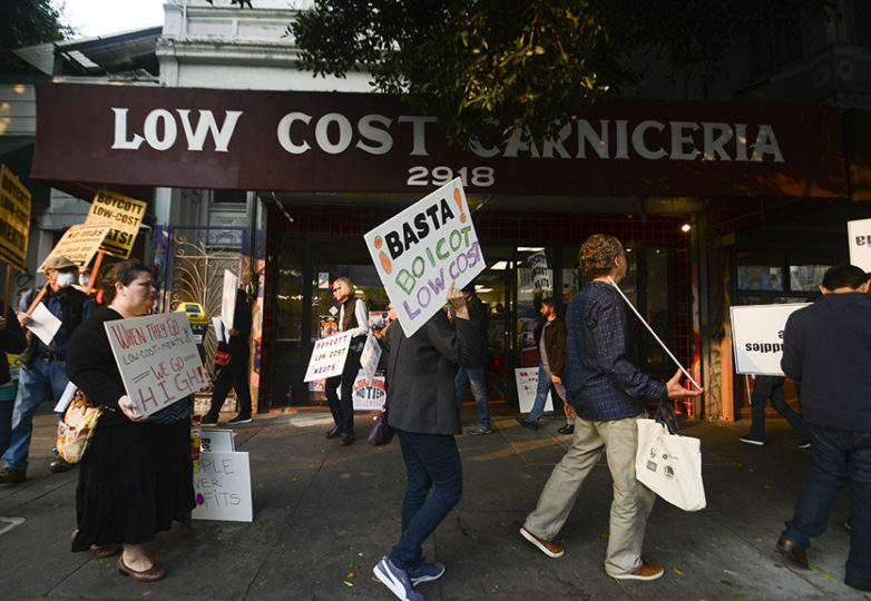 Mission residents and members of Calle 24 protest outside of Low Cost Meats at 24th and Florida streets on Nov. 10, 2018. Low Cost Meat Market's owner, Hawk Lou, also owns the property at 22nd and Mission streets, which burned down in 2015, killing one man and displacing more than 50 tenants. Lou had promised to bring tenants and businesses back after the fire by selling the property to the city, but now he is proposing to build luxury units at that site. Photo: Jocelyn Carranza