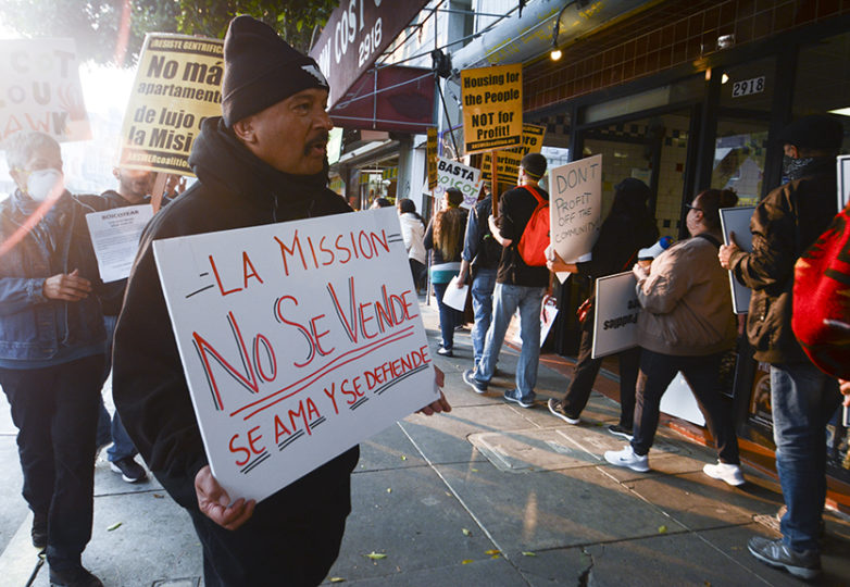 "Roberto Hernandez holds a sign reading ""La Mission no se vende. se ama y se defiende,"" ""The Mission is not for sale. It is loved and defended,"" on Nov. 10, 2018 outside of Low Cost Meats at 24th and Florida streets. Photo: Jocelyn Carranza."