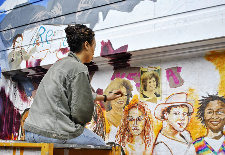 "Adrianna Adams works on the ""Women of the Resistance"" mural in Balmy Alley, San Francisco on Oct. 3, 2018. Courtesy: Daniel Valencia"