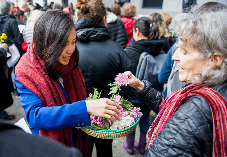 Flowers are distributed on Jan. 11 at Compassion Has No Walls, the monthly interfaith vigil for migrants and caravan members who have died while in detention. Photo: Beth LaBerge