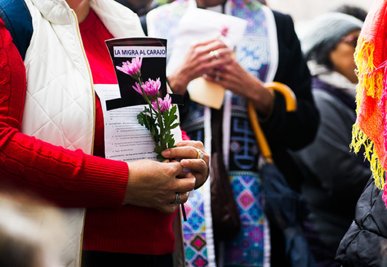 Euma Delgado holds flowers on Jan. 11 at Compassion Has No Walls, the monthly interfaith vigil for migrants and caravan members who have died while in detention, which is held outside ICE's San Francisco headquarters at 630 Sansome St. Photo: Beth LaBerge