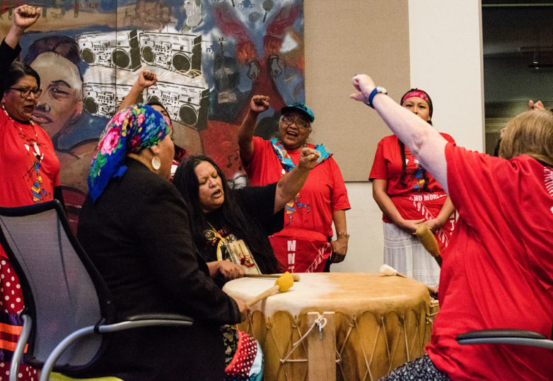 Women of the Red Lightning women's drum group raise their fists in unison during their final performance at the launching reception for Sovereign Bodies Institute, U.C. Berkeley, Jan. 18, 2019. Photo: David Mamaril Horowitz