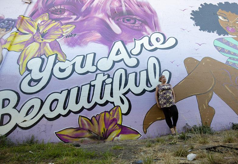 La artista Ursula X. Young frente al mural que pintó junto con sus colegas de Few and Far en las calles 24 y Willow en Oakland, el 30 de septiembre de 2018. Foto: Amanda Peterson