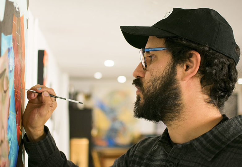 """Artist Max Marttila finishes a painting specifically made for his gallery exhibition, """"Castles Made of Fog."""" His works and others' adorn the walls of a shared art studio in the Haight, Feb. 5, 2019. Photo: David Mamaril Horowitz"""