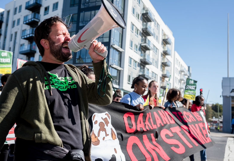 Adam Gansel, a special education teacher of Oakland Tech High School leads hundreds of staff and students in a protest chant as they march down Broadway Avenue toward Oscar Grant Plaza on Thursday, Feb. 21, 2019. Photo: Mike Chen