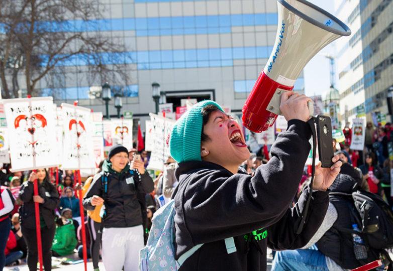 Donna Salonga, grita a través de un megáfono durante un mitin en la Plaza Oscar Grant el 21 de febrero en apoyo de los docentes de las escuelas del Distrito Escolar Unificado de Oakland, que están en paro laboral. Foto by Amanda Peterson