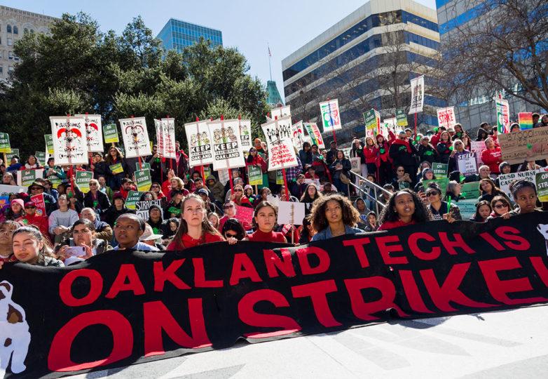 """Estudiantes en la Plaza Oscar Grant sostienen un letrero durante la marcha de los profesores en paro laboral, en el que se lee: """"Oakland Tech en huelga"""". Foto: Amanda Peterson"""
