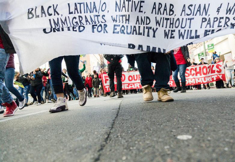 """Los estudiantes en el centro de Oakland sostienen un cartel que dice: """"Estudiantes y maestros unidos ¡Listos para participar en la educación pública, No más cierre de escuelas! ¡Grupos más reducidos! ¡Defender la educación especial! ¡No más charters! Negros, latinos, nativos, árabes, asiáticos ¡Inmigrantes blancos con y sin papeles, unidos por la igualdad, lucharemos!"""" Foto: Amanda Peterson"""