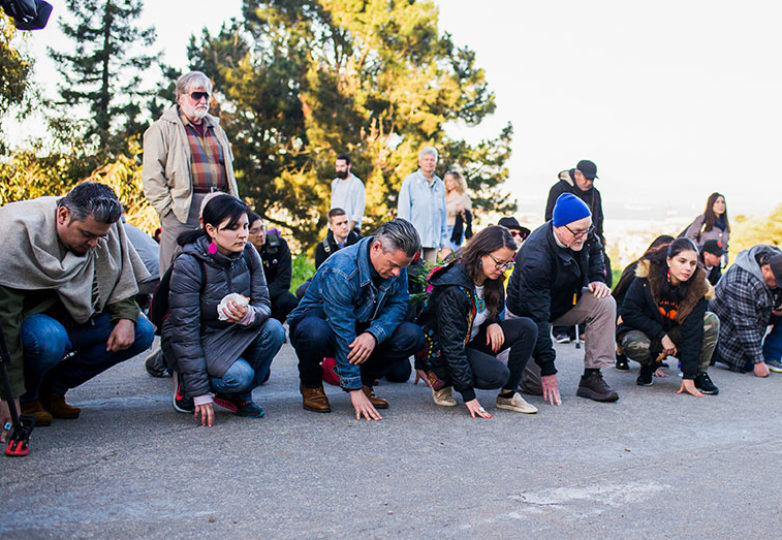 Friends and family kneel in remembrance of the death of Alex Nieto 5 years earlier, in Bernal Heights Park on Mar. 21, 2019. Photo: Beth LaBerge