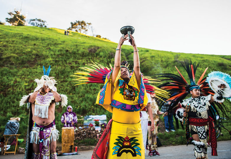 Aztec dancers perform a ceremony in remembrance of the death of Alex Nieto 5 years earlier in front of his altar, in Bernal Heights Park on Mar. 21, 2019. Photo: Beth LaBerge