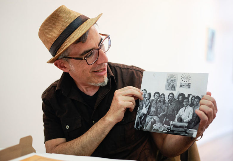 """""""Remember Los Siete"""" curator Fernando Martí holds an archival photo of the Los Siete activists. Photo: Alexis Terrazas"""