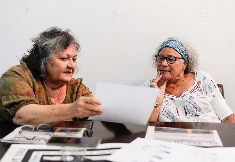 """Judy Drummond and Donna Amador view archival photos that will be displayed in the """"Remember Los Siete"""" exhibit. Photo: Alexis Terrazas"""