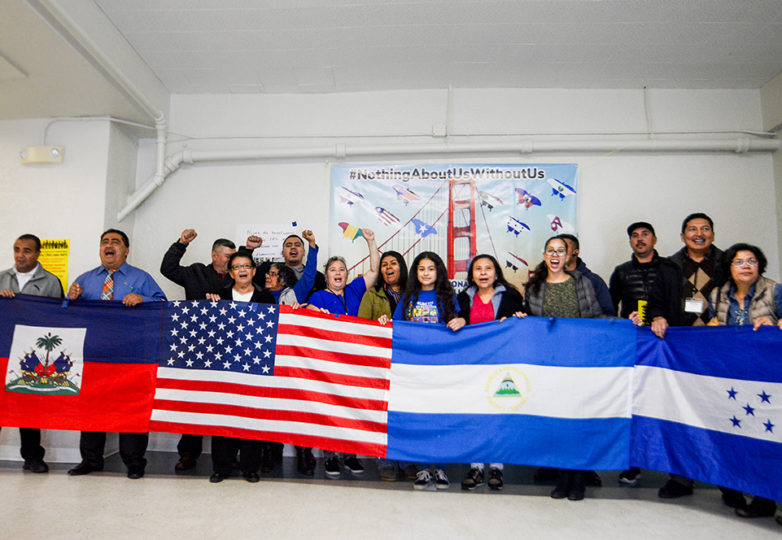 Community residents and members from National TPS Alliance, Faith in Action Bay Area, Catholic Charities and Pangea Legal Services pose for a photo holding flags from Honduras, Nicaragua, United States, Haiti, and El Salvador that are part of the Temporary Protected Status program (TPS) at La Iglesia San Antonio de Padua in San Francisco, March 10, 2019. Photo: Jocelyn Carranza
