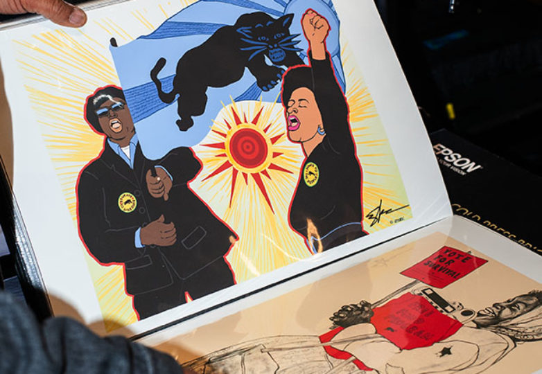 Emory Douglas flips through a portfolio of archived poster designs he created for the Black Panthers in the 1970s, San Francisco, April 9, 2019. Photo: Natasha Dangond