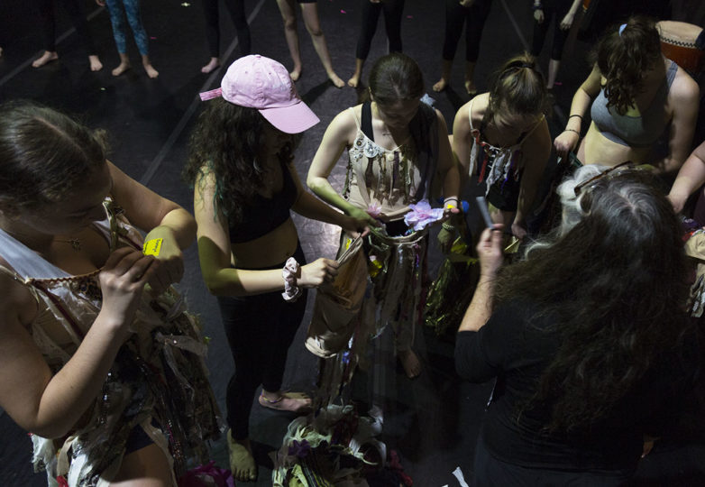 Krissy Keefer, co-founder of Grrrl Brigade passes out costumes to the girls during a dress rehearsal at Dance Mission Theatre on April 7, 2019. Photo: Amanda Peterson