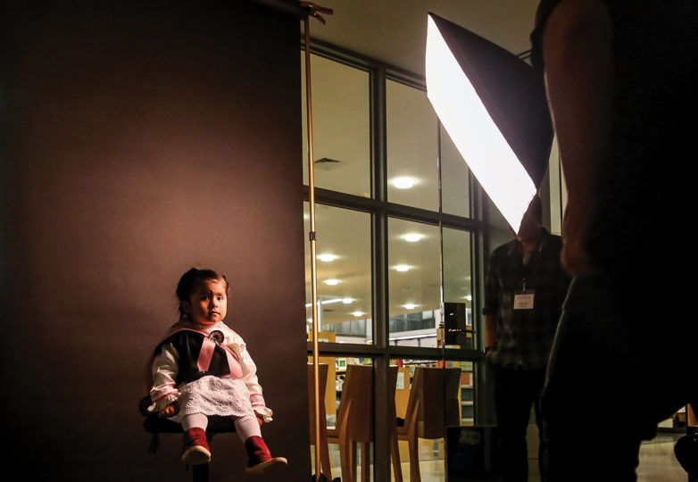 Mayeux Red Eagle Zavala, daughter of Mytia Zavala, the executive director of American Indian Film Institute, gets photographed by Jean Melesaine inside the San Francisco Public Library for the Pioneer Monument Project on April 5, 2019. Photo: Adelyna Tirado