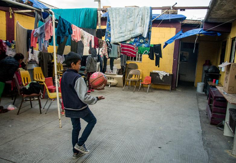 A boy kicks a soccer ball as he walks through the main common outdoor area at Camino de Salvación church and shelter, March 10, 2019. Photo: Mabel Jiménez