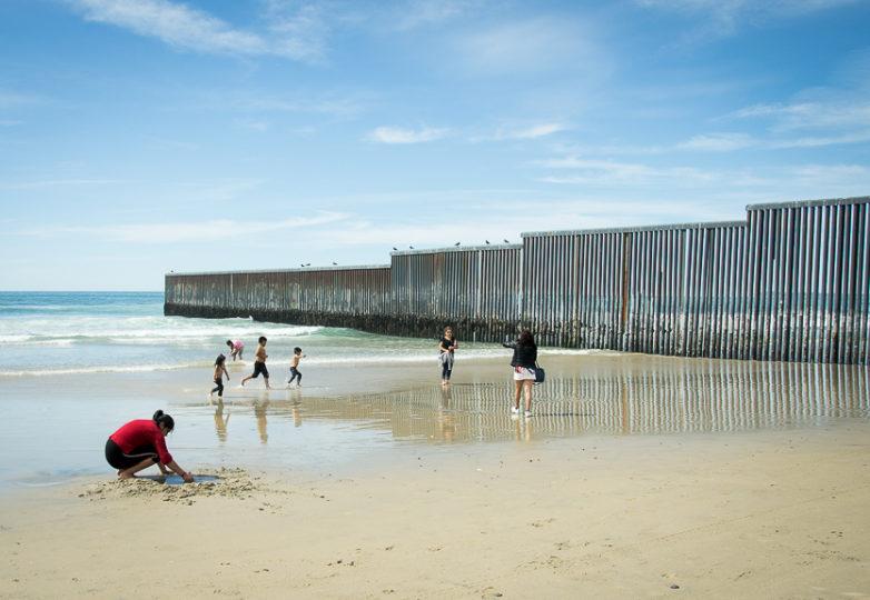 Niños corren en la playa cerca del límite oeste del muro fronterizo. Foto: Mabel Jiménez