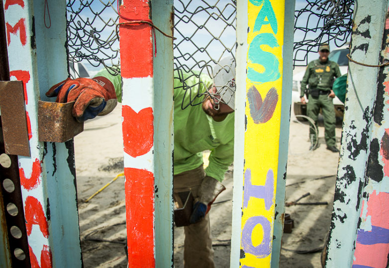 Welders make repairs to a section of the US/Mexico border wall as CBP agents keep guard at Playas de Tijuana, March 15, 2019. The day prior, migrants used a carjack to open the space between the beams, and wire cutters on the chain link fence in between the beams. Photo: Mabel Jiménez