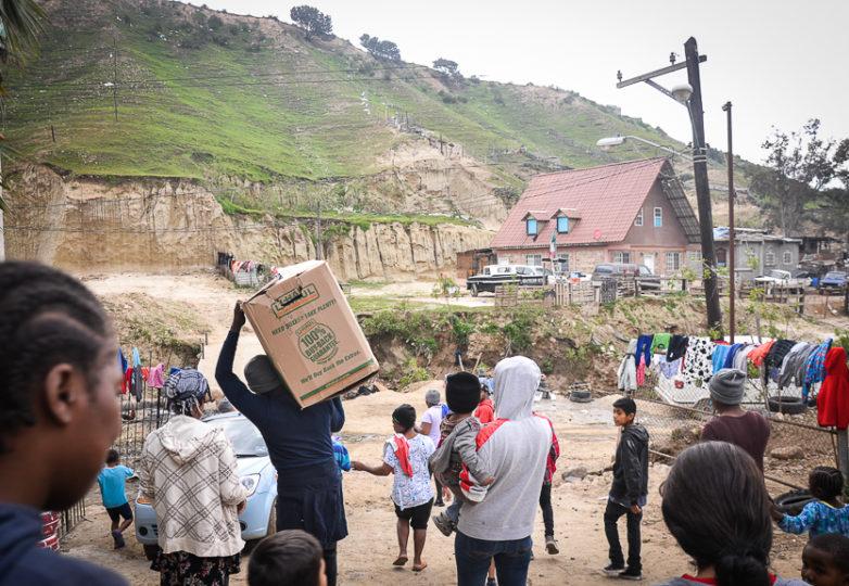 Los miembros de la comunidad llevan cajas de donaciones a un área de distribución en el edificio principal de la iglesia Embajadores de Jesús, también conocida como Little Haiti, en el barrio Cañón del Alacrán en Tijuana, México, el 26 de febrero de 2019. Foto: Mabel Jiménez