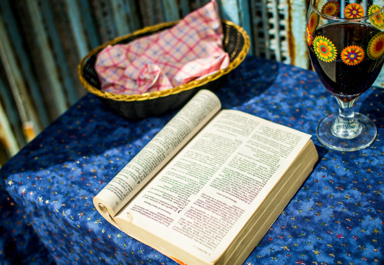 """A book titled """"La Palabra de Dios"""" (""""The Word of God"""") along with bread and wine, sit on a table set up against the U.S.-Mexico border wall at Playas de Tijuana, in preparation of a bilingual binational mass service on March 10, 2019. Photo: Mabel Jiménez"""