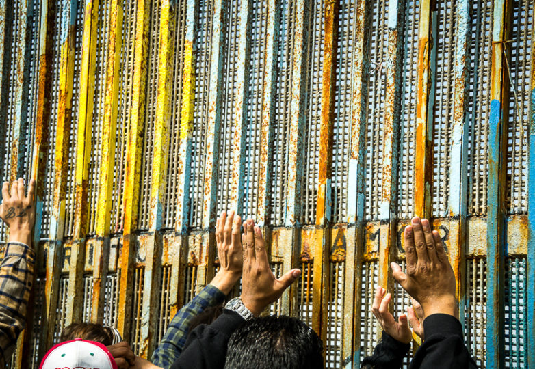 Attendees at a bilingual, binational sermon for Sunday mass by the U.S.-Mexico border at Playas de Tijuana, reach for the border wall as a sign of unity, March 10, 2019. Photo: Mabel Jiménez