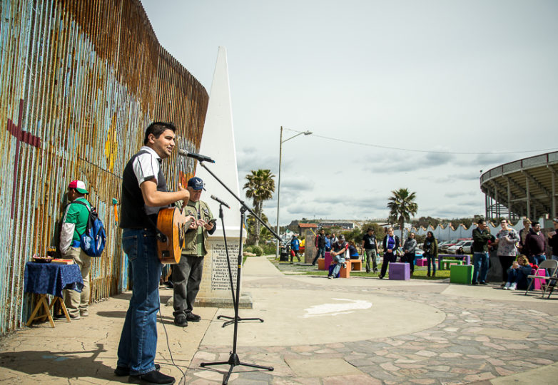 A musician sings christian songs during a bilingual, binational sermon for Sunday mass by the U.S.-Mexico border at Playas de Tijuana, Sunday March 10, 2019. Photo: Mabel Jiménez
